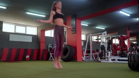 Una muchacha deportiva salta la cuerda en el gimnasio La muchacha hermosa en el club de deportes hace el diferente tipo de ejerci metrajes