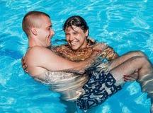 Una muchacha detiene a un individuo en sus brazos mientras que se coloca en la piscina Fotografía de archivo