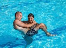 Una muchacha detiene a un individuo en sus brazos mientras que se coloca en la piscina Imagen de archivo libre de regalías