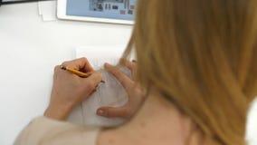 Una muchacha dibuja en los bosquejos de papel de la ropa metrajes
