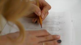 Una muchacha dibuja en los bosquejos de papel de la ropa almacen de metraje de vídeo