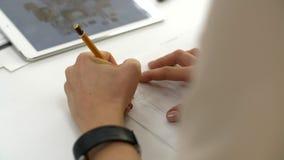 Una muchacha dibuja en los bosquejos de papel de la ropa almacen de video