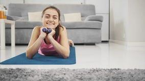 Una muchacha disfruta de aptitud en casa mientras que sonríe