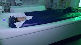 Una muchacha disfruta del procedimiento del masaje hidr?ulico y de abrigos con chromotherapy en balneario almacen de metraje de vídeo