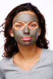 Una muchacha divertida con la máscara del fango Imagenes de archivo