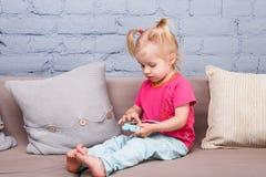 Una muchacha divertida de dos años del nacimiento con el pelo blanco y en una camisa roja y pantalones azules juega un teléfono m Fotografía de archivo