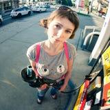 Una muchacha divertida que sostiene el surtidor de gasolina en la gasolinera Imágenes de archivo libres de regalías