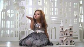 Una muchacha dulce en un vestido brillante gris se sienta cerca de un palacio del juguete y envía un beso del aire, una tarjeta d metrajes