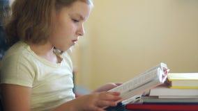 Una muchacha dulce está preparando lecciones Libros de lectura El enseñar casero Educación de niños Día de conocimiento almacen de metraje de vídeo