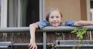 Una muchacha dulce se está sentando en el balcón metrajes