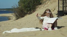 Una muchacha dulce se sienta en la arena y lee movimientos de un libro un perro almacen de video