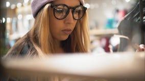 Una muchacha elegante del inconformista viene al estante de la tienda y elige los nuevos vidrios tiro borroso metrajes