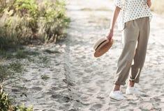Una muchacha elegante en pantalones beige ligeros y con un sombrero de paja en sus manos Fotografía de archivo libre de regalías