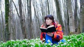 Una muchacha elegante hermosa está leyendo un libro interesante en un bosque de la primavera por completo de snowdrops florecient metrajes