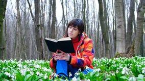 Una muchacha elegante hermosa está leyendo un libro interesante en un bosque de la primavera por completo de snowdrops florecient almacen de metraje de vídeo