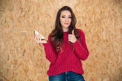 Una muchacha elegante joven sonríe suavemente y muestra su pulgar para arriba, significando que su bocadillo es muy sabroso, y us Imagenes de archivo