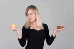 Una muchacha elige entre una manzana y una torta Imagen de archivo libre de regalías