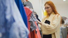 Una muchacha elige un vestido rayado en una tienda de ropa del ` s de las mujeres Imagen de archivo