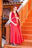 Una muchacha embarazada joven que se coloca en las escaleras Fotos de archivo libres de regalías