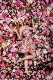 Una muchacha emocional hermosa con el ramo de las flores cerca de un wa floral Imagen de archivo