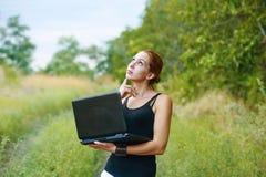 Una muchacha emocional joven con el ordenador portátil en el parque Imágenes de archivo libres de regalías