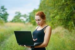 Una muchacha emocional joven con el ordenador portátil en el parque Foto de archivo libre de regalías