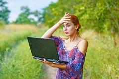 Una muchacha emocional joven con el ordenador portátil en el parque Imagenes de archivo