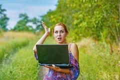 Una muchacha emocional joven con el ordenador portátil en el parque Fotografía de archivo