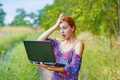 Una muchacha emocional joven con el ordenador portátil en el parque Imagen de archivo