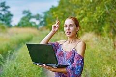 Una muchacha emocional joven con el ordenador portátil en el parque Fotografía de archivo libre de regalías