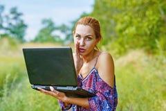 Una muchacha emocional joven con el ordenador portátil en el parque Foto de archivo
