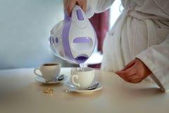 Una muchacha en una albornoz por la mañana vierte té en las tazas imagen de archivo