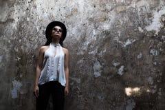Una muchacha en una blusa blanca, con la vicia destruyó el edificio Helouin Foto de archivo