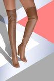 Una muchacha en botas con un alto color del caramelo del palillo hessian imagenes de archivo