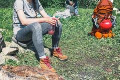 Una muchacha en caminar las botas, disfrutando del resto en acampar Imagen de archivo libre de regalías