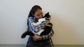 Una muchacha en una camisa de tela escocesa abraza su gato blanco y negro preferido El gatito rechoncho no es muy feliz con tal d almacen de video