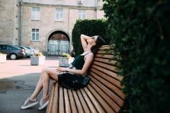 Una muchacha en una camisa negra y pantalones cortos en un parque en un banco imagenes de archivo