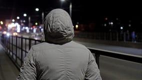 Una muchacha en una capa gris con una capilla en va en la noche en el puente Visi?n desde La c?mara est? en el movimiento Aparato almacen de video