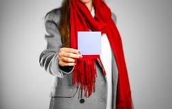 Una muchacha en capa gris y bufanda roja sostiene un limpio azul claro vacia imagen de archivo