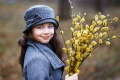 Una muchacha en capa gris y un sombrero gris lindo en el bosque en primavera temprana con una rama del sauce de las ramitas que h Imagen de archivo libre de regalías
