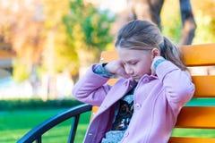 Una muchacha en una capa rosada se endereza el pelo se sienta en un banco amarillo en el parque fotografía de archivo