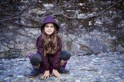 Una muchacha en una capilla se sienta en un fondo gris de la roca Foto de archivo libre de regalías