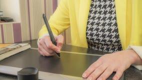 Una muchacha en una chaqueta amarilla dibuja en la tableta imagen de archivo