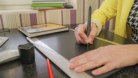 Una muchacha en una chaqueta amarilla dibuja en la tableta fotos de archivo libres de regalías