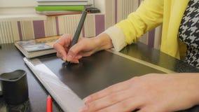Una muchacha en una chaqueta amarilla dibuja en la tableta fotografía de archivo libre de regalías