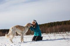 Una muchacha en una chaqueta de esquí verde en sus rodillas y un perro blanco ruso en un campo nevoso en invierno soleado fotografía de archivo libre de regalías