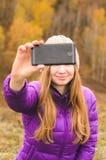 Una muchacha en una chaqueta de la lila hace un salfi en una montaña, una visión de las montañas y un bosque otoñal por un día nu Imagen de archivo libre de regalías