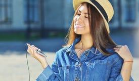 Una muchacha en una chaqueta del dril de algodón camina alrededor de la ciudad en un sombrero de paja con un teléfono en sus mano imagen de archivo