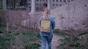 Una muchacha en una chaqueta del dril de algodón y pantalones del dril de algodón está en la parcela vacante debajo del puente Ig almacen de metraje de vídeo