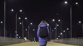 Una muchacha en una chaqueta del invierno camina con haber abandonado, ciudad de la noche almacen de metraje de vídeo